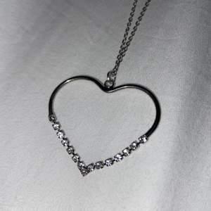 Ett halsband med ett hjärta och små stenar. Aldrig använt. Köpt för ca 200kr och säljer för 90 inklusive frakt.
