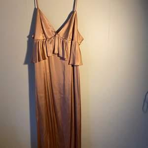 """En beige siden klänning med oranga/bruna toner från HM som aldrig är använd. Klänningen är rak men har en """"volang"""" vid bysten. Den är V-ringad med smala band som är justerbara"""