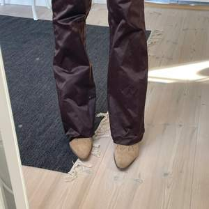 Säljer dessa jättefina bruna satin byxor som är second hand. Storleken i är 32 men de sitter absolut inte så utan snarare som 35-38. Jag brukar ha 36/38. De är lite för korta för mig som 177, har sprätt upp de där nere. Skulle säga att de passar någon som är 175cm och neråt. Skriv om ni har några frågor🤩
