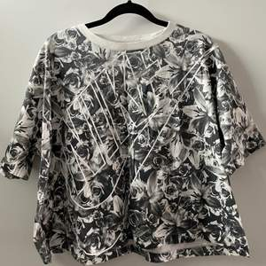 En rosmönstrad croppad t-shirt från Nike med vit tryck på framsidan. Knappt använd
