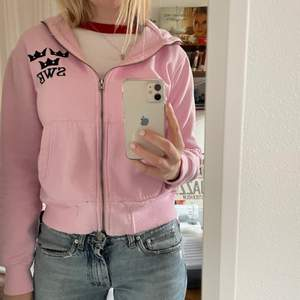 Ljusrosa zip up hoodie med texten SWE och tre kronor, står också sweden upp och ned på luvan. Köpte second hand, den är använd och lite nopprig men väldigt skön. Kan mötas i Stockholm annars betalar köpare frakt.