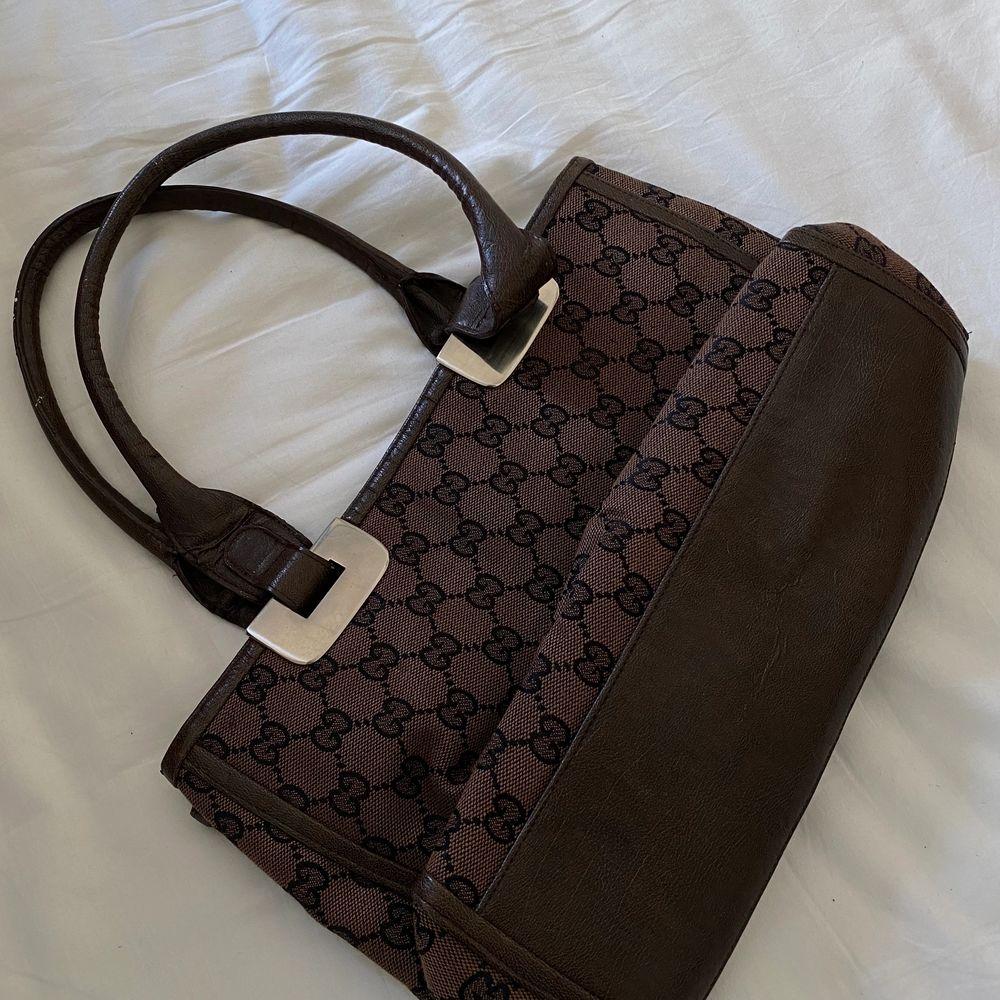 Fake gucci-väska, i brun färg! Supersnygg och passar fint nu till sommarens outfits! Helt ny! Så väldigt fint skick! Buden är BINDANDE . Väskor.