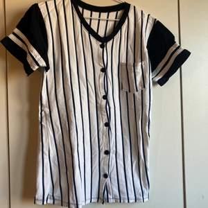 Supercool retro t-shirt med knäppning. Baseball stil. Köpt på second hand affär i Berlin. Mkt bekväm men tyvärr för liten för mig. Vit och mörkt blå. Flyttrensning! Samfraktar såklart vid köp av flera plagg. Som med allt jag säljer går hälften av pengarna till läkare utan gränser.