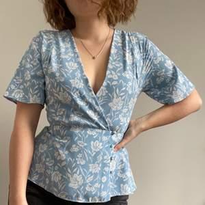 Fin blå blus med vitt blommönster! Använd en gång så den är i nyskick. Har tyvärr blivit för liten för mig. Sitter fantqstiskt bra och urringningen är inte för mycket. För mer frågor eller bilder är det bara skriva ett meddelande☀️