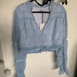 Så fin blå/vit blommig blus från Pamela X NAKD strl 40. Aldrig använd. Prislapp kvar. Köparen står för frakten.