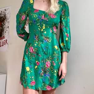 Säljer denna ursnygga gröna klänning med blommor. Man knäpper den i mitten och den har smått puffärmar. Köpt på WAREHOUSE, storlek S/M 💚🌟