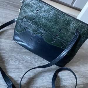 Skinnväska köpt vintage i grönaktig färg och svart. Den är använd några gånger av mig men är i jättebra skick. Eftersom det är skinn så är väskan snyggt sliten. FRAKT ÄR INKLUDERAT I PRISET. ⚡️⚡️