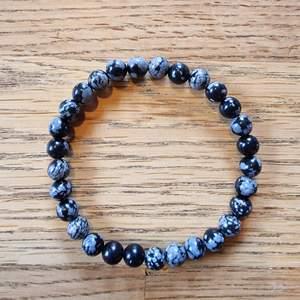 Armband med 6 mm stora kristallpärlor av snöflingeobsidian. Rundslipade stenar trädda på elastisk tråd. Ca 16 cm omkrets. Skickas i vadderat kuvert via postnord.