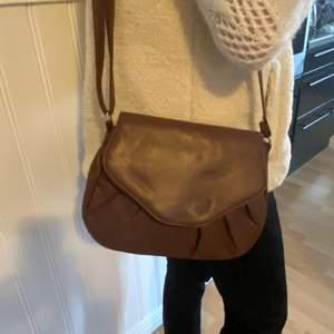 Vintage väska i konstläder som ej kommer till användning. Fack med dragkedja invändigt. 115 cm långt band som kan kortas ned.