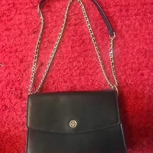 Säljer väska från Tory Burch i mycket bra skick. Väskan är svart med gulddetaljer. Bandet går att reglera i två längder (se bilder). Vid intresse kan jag självklart skicka fler bilder.