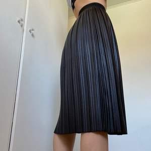 Helt oanvänd plisserad kjol i fakeläder från Chiquelle! Stl 36 men kan passa 34 samt 38 då det är resår i midjan. Nypris: 300kr