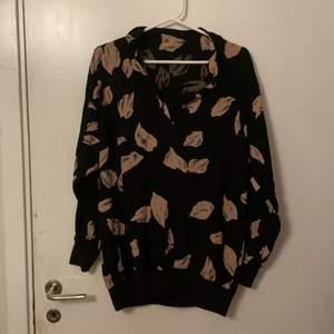 Svart tröja med rosa blommblad, står inte vart den är ifrån eller storlek men skulle säga medium