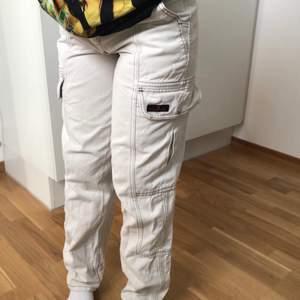 """Beiga """"cargopants"""" med sydda detaljer och fickor vid benen. Storleken är 25 vid midjan och 32 i längden. Brukar vanligtvis ha XS/S och de passar."""