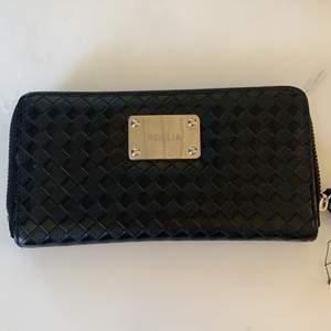 En svart fin med fem fack varav ett är för mynt samt 8 fack för sina kort. Den har aldrig används. Kan fraktas men då står köparen för den kostnaden.