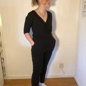 Supersnygg svart byxdress med fickor (!!!) och djup urringning. Bra skick! Från Bik Bok