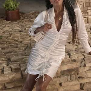 """Slutsåld vit silkes klänning i vit färg med rynkningar i mitten, krage och snören ner till i storlek M. Ny och oanvänd. Det går inte att justera rynkningarna, snöret är endast som """"dekoration"""". Perfekt för studenten om man vill ha något speciellt. Om fler är intresserade så vinner högsta bud. (Jag brukar ha XS-S men den här klänningen satt bra) ser bäst ut efter strykning!"""