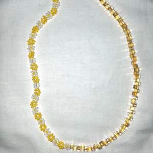 Modernt och populärt pärlat halsband, halva sidan med gula och vita blommor och andra sidan med gula japanska glaspärlor. Se gärna mina andra annonser för fler halsband och ringar.