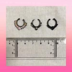 Tre fake-septum-piercingar. Alla går att böja till önskade storlekar. Den vänstra saknar en sten (se bild 3). Rengörs noggrant innan frakt! Köps endast tillsammans. Frakten ingår i priset :)