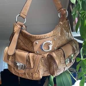 Säljer denna MAGISKA handväska/ axelväska i nyskick. Från GUESS, kan dock inte garantera att den är äkta då den är köpt secondhand  🧚🏻🧚🏻🌟 Inga skador eller slitningar, fräsch på både insida och utsida. Praktisk axelväska med många fack!! Rejält material. Ger 2000s Vibes. Skick: 10/10