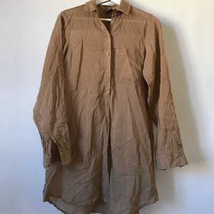 Superskönt skjortklänning eller längre skjorta från Melmelli. Beige mot brun, luftig och behaglig och knappar halvvägs. Förmodligen bomull. Märkt storlek S, men tror både XS och M fungerar utmärkt!  Skickas mot fraktkostnad eller hämtas i Stockholm! ✨🌸✨