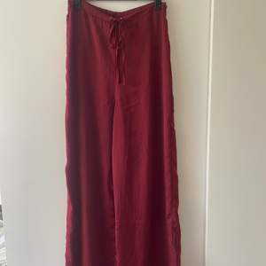 "Vinröda byxor i ""silkesmaterial"". Stl S, frakt tillkommer."
