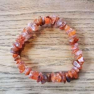 Armband med kristallpärlor av karneol. Chipsformade stenar trädda på elastisk tråd. Ca 16 cm omkrets. Skickas i vadderat kuvert via postnord.