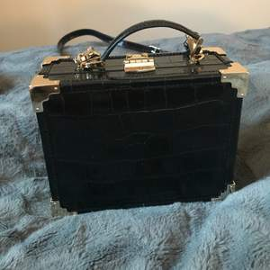 Like new! Aspinal of London classic trunk in black croc leather with red interior. Comes with dustbag and crossbody strap. Perfect condition, only worn a couple of times. Original price over 5000 SEK. Purchased from Vestiaire Collective.