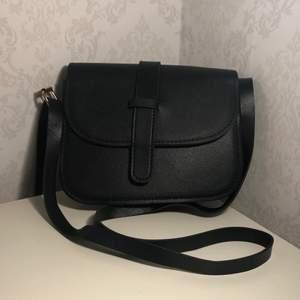 En svart justerbar väska. Väskan har bara legat i sin förpackning, anlig använd🌸