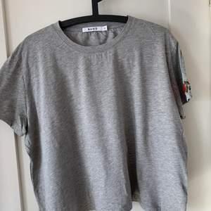 En grå t-shirt från na-kd i lite bredare modell, med en röd blomma på ena ärmen, något noprig men inget som syns så mycket. Frakt tillkommer