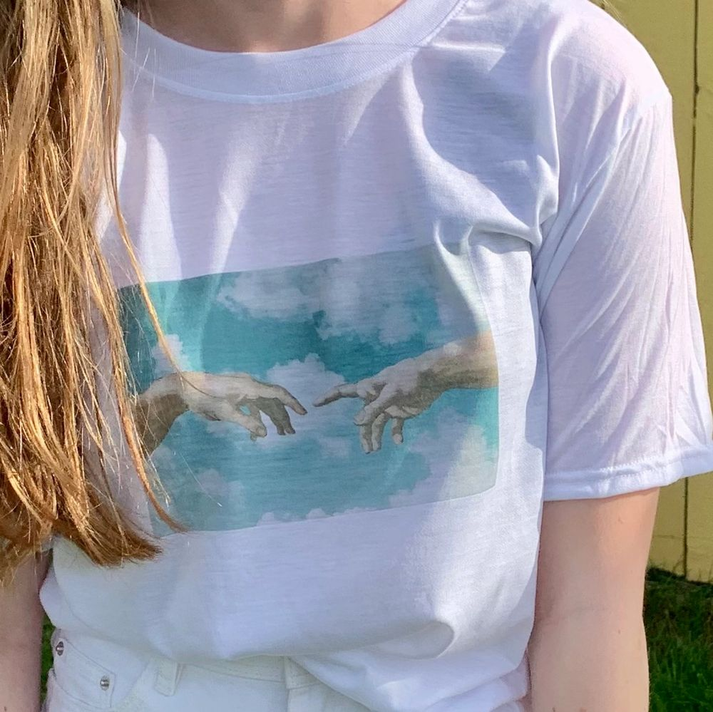 Vit T-shirt med tryck. Storlek medium. Skönt och luftigt tyg. Knappt använd alls. Trycket är inspirerat av Michelangelos Creation of Adam händerna men med en himmel som bakgrund 💙. T-shirts.