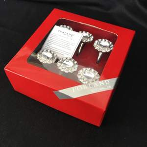 Napkin ring set from Porland Style. The set was produced in 2010. It has never been used. It has been unboxed only a few times for metal maintenance.  The set consists of 6 rings. Each ring has 1 oval cut, large size CZ (Cubic Zircon) crystal stone and 12 circles faceted cut, small size CZ (Cubic Zircon) crystal stone.  The rings are made of 1st quality brass and covered with a special shiny metal.  The set is original and has never been used. The set contains the manufacturer's cleaning and maintenance instructions.  Stone size: Big stone: 1.3 x 1.8 cm Small stones: 0.5 x 0.5 cm  1 ring weight: 25 gr Box weight: 250 gr  ISBN: 8690947430460 Product Code: 1PO114 04POR022466     https://youtu.be/SMaS1kI28C0