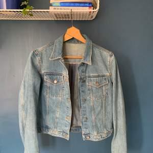 Blå jeansjacka från & other stories med knäppning på framsidan och dragkedja baktill. Fint skick, använd av mig och enbart använd ett fåtal gånger av tidigare ägare.
