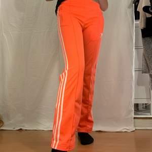 Orangea byxor med vita streck från Adidas. Fint skick.