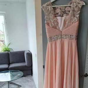 En lång ljus rosa klänning med diamant liknande pärlor på. Icke genomskinlig och inbyggda kupor finns, perfekt för bal och bröllop. Har använts en gång tidigare och är i bra skickt. Orginala pris, 2 000kr. Kontakta för mer info.