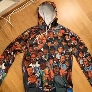 Hoodie i 100% polyester med rap-motiv. Rak ganska tailored modell. OBS NY!