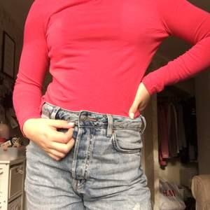 En långärmad rosa/röd tröja. Om fler är intresserade blir det budgivning i kommentarerna.