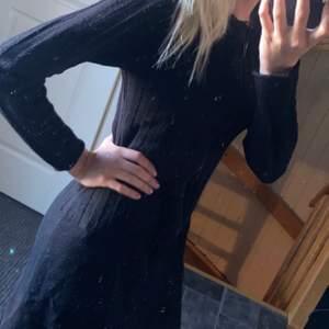 En svart stickad klänning med dragkedja. Storlek M.