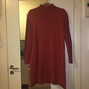 Koppar/orange färgad klänning med ribbade ärmar, hög hals och knappar längs axeln på vänster sida. 145-150 cm lång. 95% bomull och 5% kashmir. Kan mötas upp alt. skicka.