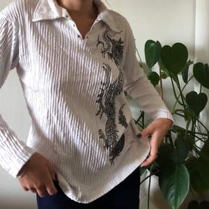 Super fin vintage tröja med krage och ett stort drak tryck på sidan. Tröjan är köpt från humana och är i väldigt bra skick. Köparen står för frakten💗💗