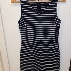 Svart och vitrandig kort klänning med dragkedja baktill. Står att det är storlek xs men passar förmodligen S/M också.