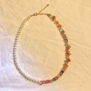 Halsband med olika kristaller och vita pärlor. Låset är 24k guldpläterat🌟
