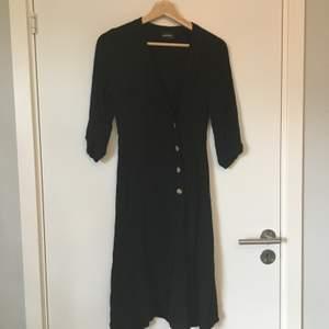 Svart klänning med omlottknäppning från Monki. Tror det är storlek XXS men kan också vara XS, lappen saknas. Gott skick. Frakt betalas av köparen.