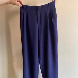Kostymbyxor i en lite mörkare blå färg. Sitter perfekt runt rumpan och blir sedan lösa, raka på benen. Finns fickor på sidorna och två fejk baktill. Tyvärr passar de inte mig längre men detta är ett riktigt bra köp!