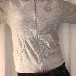 En grå vanlig kofta med en silvrig krona vid bröstet. Från hm.