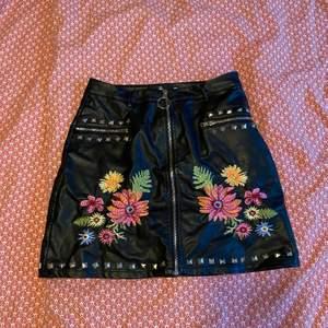 Läder midje kjol med detaljer. Nitar och även broderade blommor på. Storlek 38