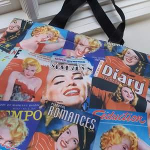 Supersnygg väska men Marilyn Monroe motiv på. Handtagen är 20cm långa och går utmärkt att ha på axeln, i armvecket eller i handen. Inuti är det som ett stort fack. Cool detalj med stenar på framsidan som skriver Marilyn. Botten är 12x28cm. Buda från 80kr