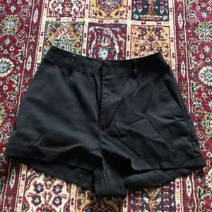 Shorts med hög midja. Dubbelknäppning och dragkedja. Fickor i sidorna, Fuskfickor bak.