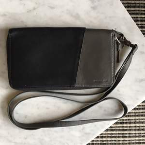 Plånbok/väska i läder från The Local Firm. Fungerar även utmärkt som reseplånbok! Lång avtagbar axelrem.