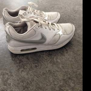 Nike -sneakers vita med silverdetaljer.  Fint skick. Endast använda ett fåtal gånger