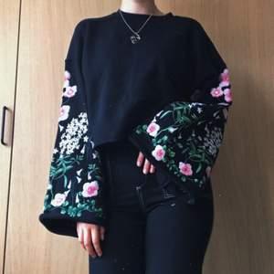 """Superfin och trendig tröja från H&M i sweater material med broderade ärmar. Brodyren föreställer rosa blommor och gröna blad med guldiga detaljer. Ärmarna är stora och """"utsvängda"""". Passar bra till vardags eller som finkläder 🌺🌺"""